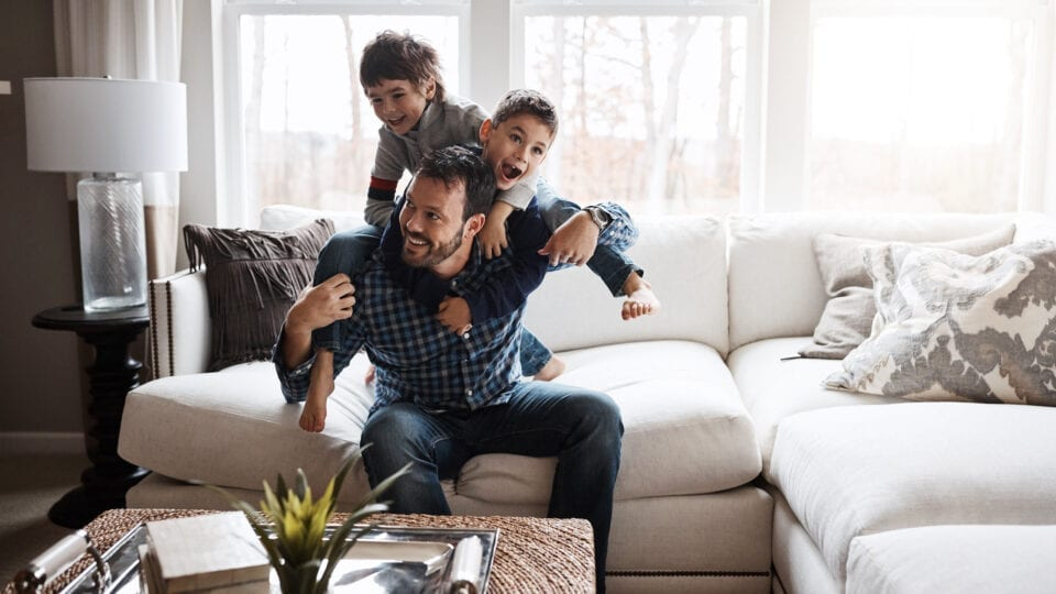 Father with two boys playing on a couch