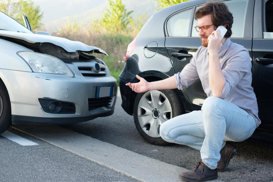 Man on phone dealing with fender bender