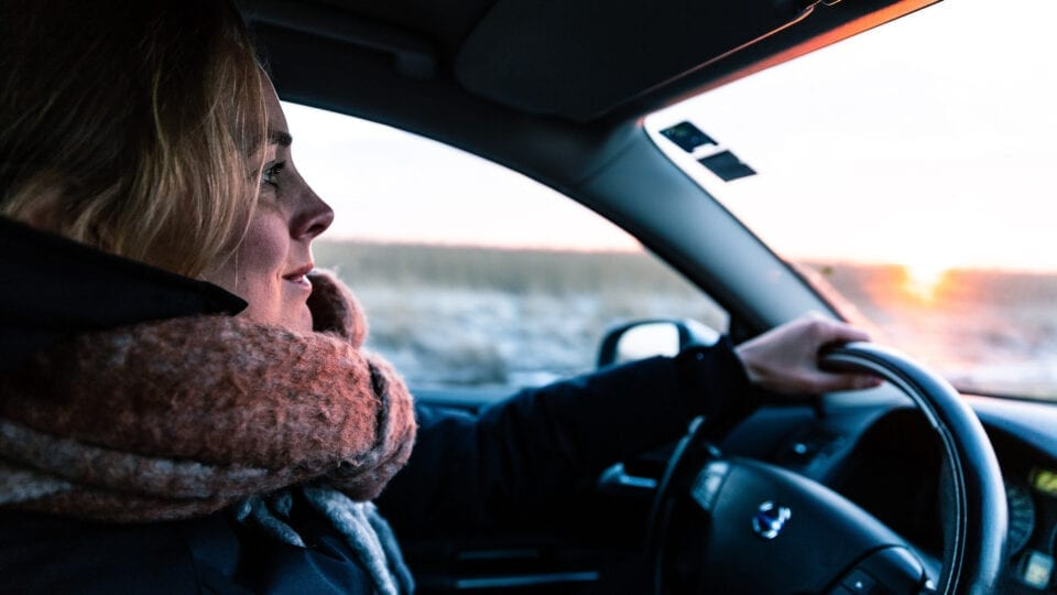 Woman driving in a car at sunset